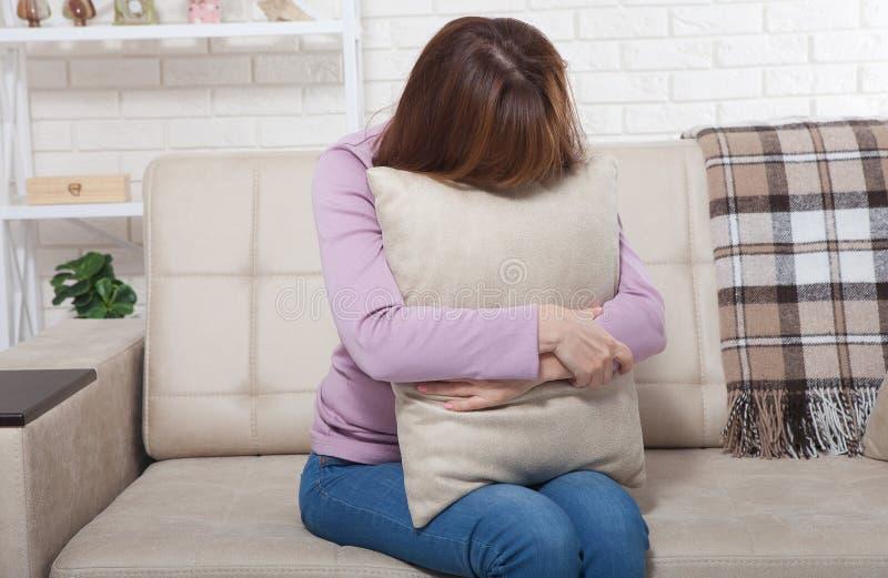 美好的中部变老了拿着枕头和哭泣在沙发的深色的妇女 家庭背景 更年期时间 免版税库存图片
