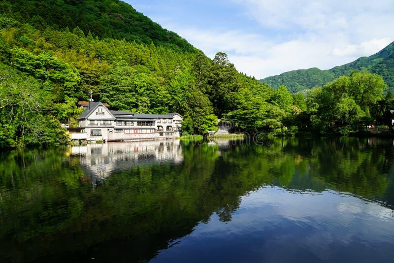 美好的丰富的自然绿色在新鲜的湖Kinrin的山风景对称反射有在春天期间的大厦的 免版税库存照片