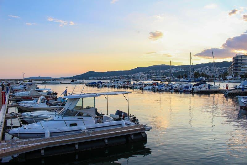 美好的五颜六色的日落在城市戏曲,有小船的希腊港口  免版税库存照片