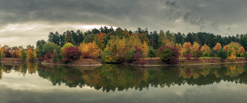 美好的五颜六色的秋天 城市公园的美丽如画的全景有在多云的河反映的多彩多姿的树的 库存照片
