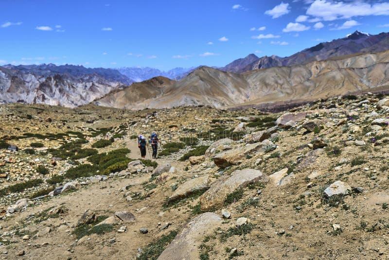美好的五颜六色的风景选择聚焦与两个游人的在Markha谷轨道之后在喜马拉雅山,拉达克,印度 库存图片