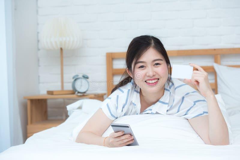 美好的亚洲夫人用途聪明的手机和信用卡在床上 网上预定或网上商业概念 免版税图库摄影