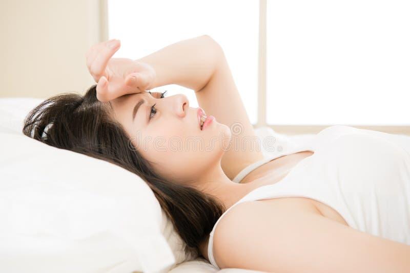 美好的亚洲妇女感受不适的憔悴和不适 免版税图库摄影