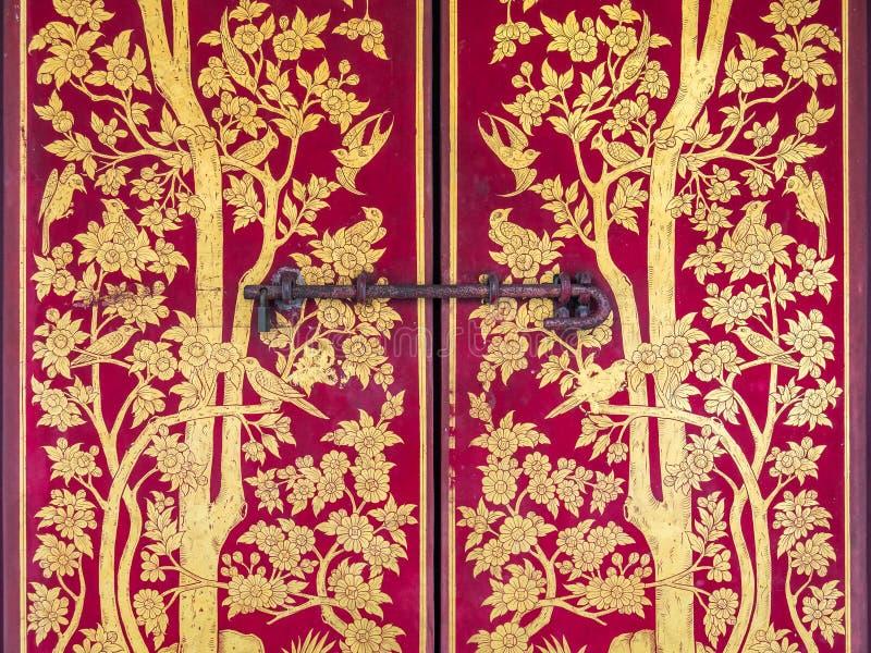 美好的传统泰国样式金在一个红色木门的绘画和树细节与鸟的在曼谷玉佛寺,曼谷大皇宫, 库存照片