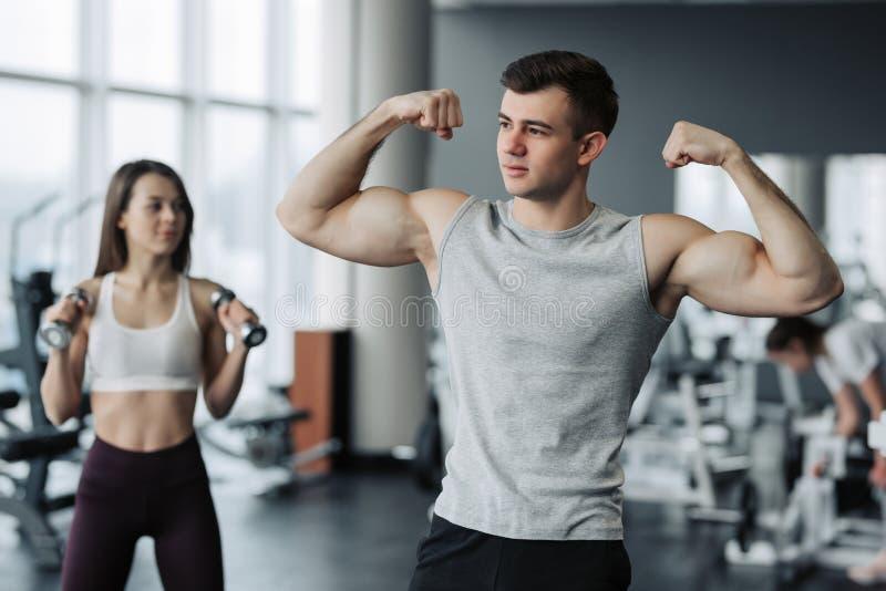 美好的体育夫妇在健身房时显示他们的肌肉,当站立 免版税库存照片