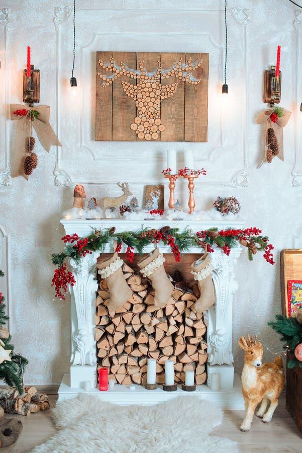 美好的假日装饰了室有圣诞树的,壁炉和有礼物的 舒适冬天场面 内部白色 库存照片