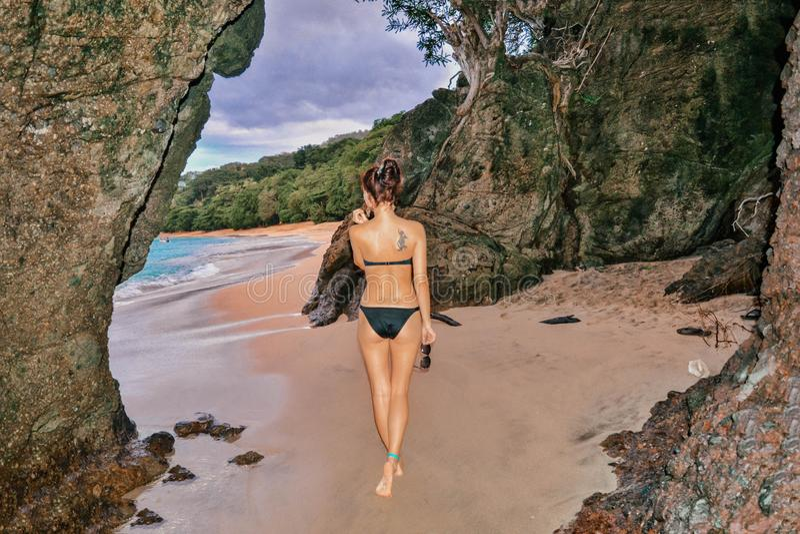 美好的健身式样摆在海滩的一个洞 库存照片
