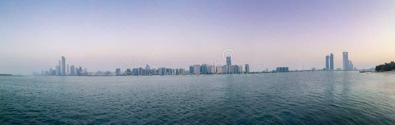美好的全景射击了阿布扎比市地平线塔和海滩在日落 免版税库存照片