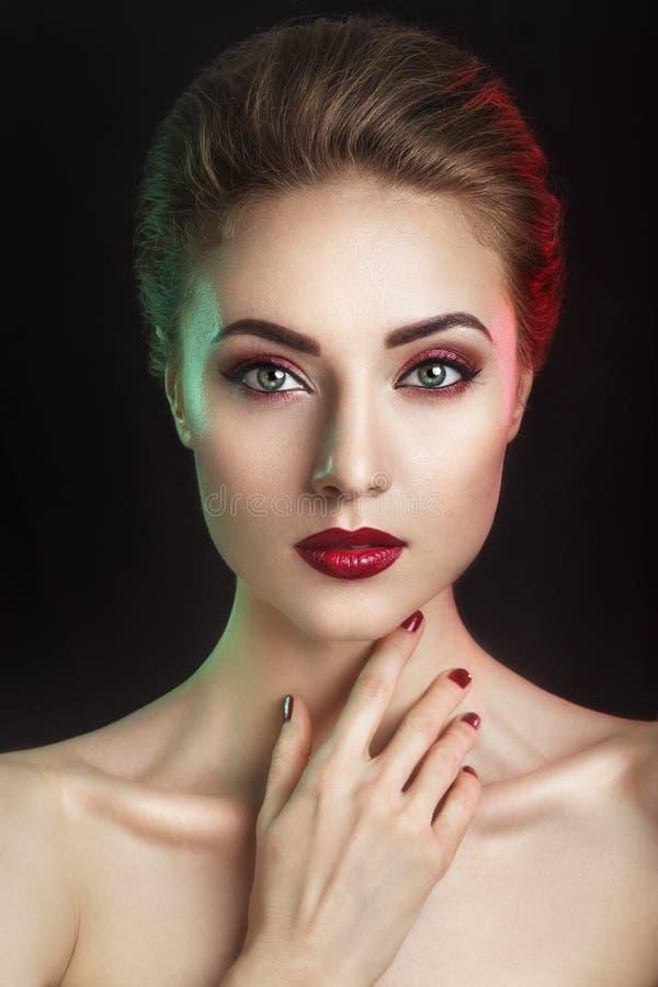美好的典雅的年轻模型与红色嘴唇和颜色晚上化妆 在黑暗的背景的妇女面孔 在演播室拍的照片 库存照片