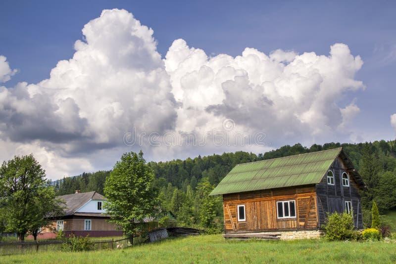 美好的农村夏天风景在明亮的晴天 由太阳两好的木传统乌克兰房子的升,住宅和为 免版税库存图片