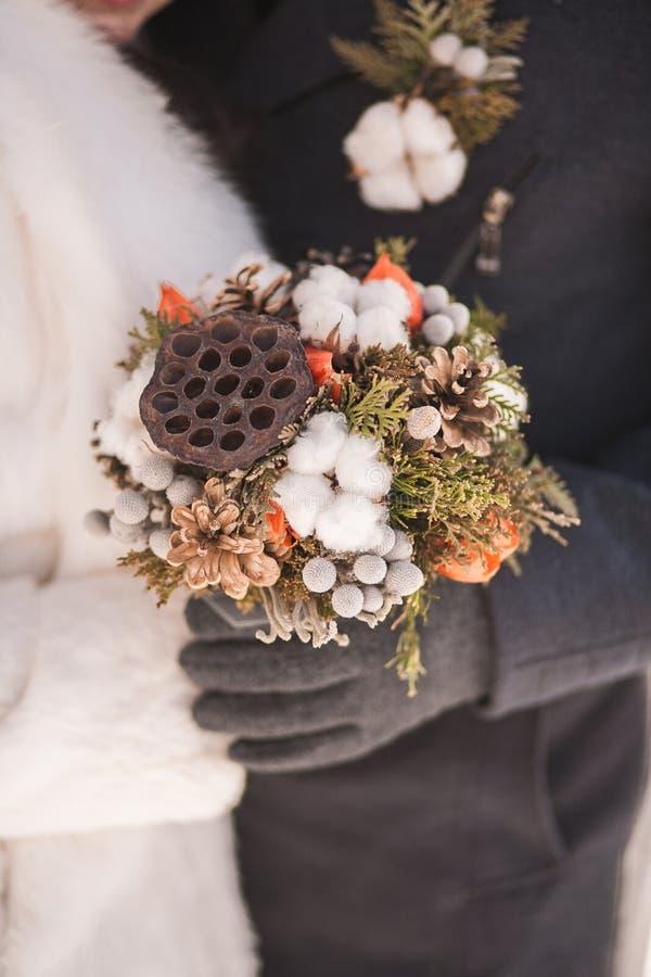 美好的冬天新娘婚礼花束在手上 库存照片