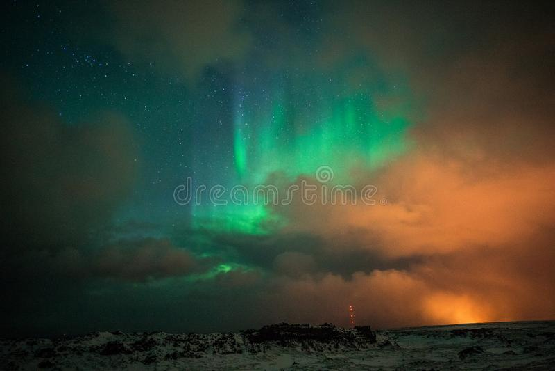 美好的北极光在云彩后的冬天在冰岛 库存图片