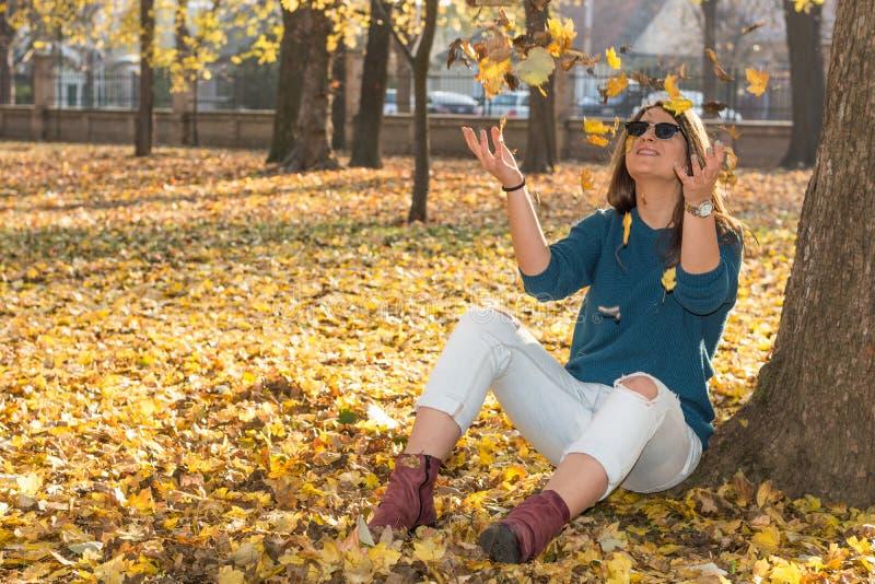 美好的十几岁的女孩捉住的下跌的秋天黄色离开 免版税库存图片