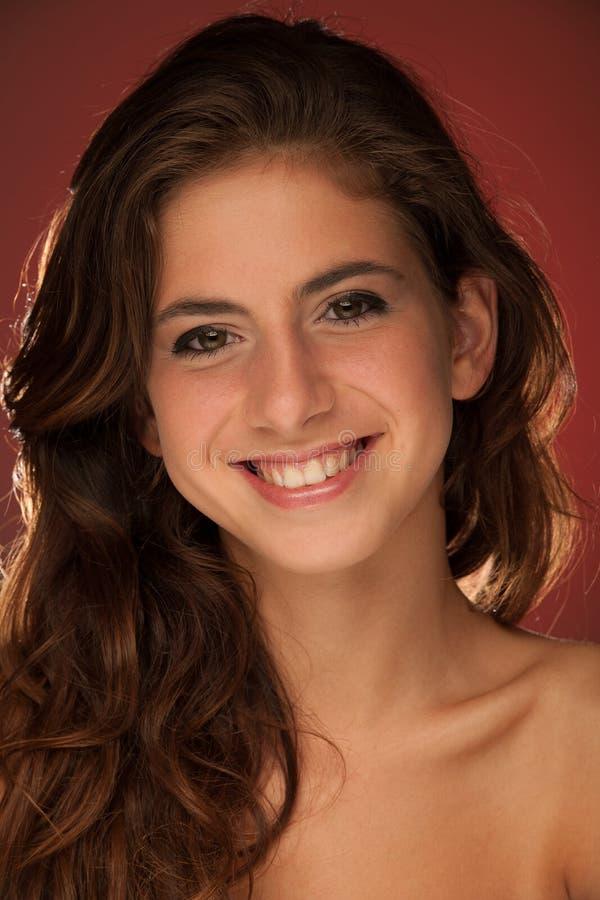 美好的十几岁的女孩红色背景秀丽画象  免版税图库摄影