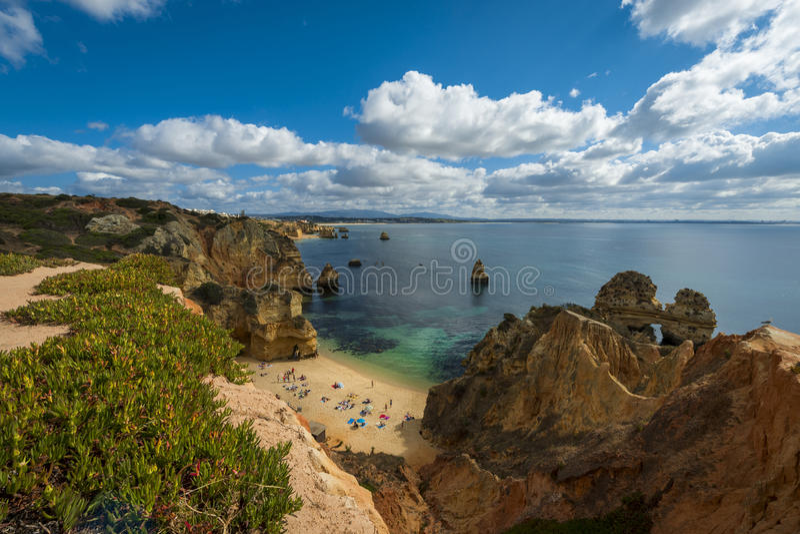 美好的卡米洛海滩普腊亚的人们在拉各斯,葡萄牙做卡米洛和周围的峭壁 库存图片