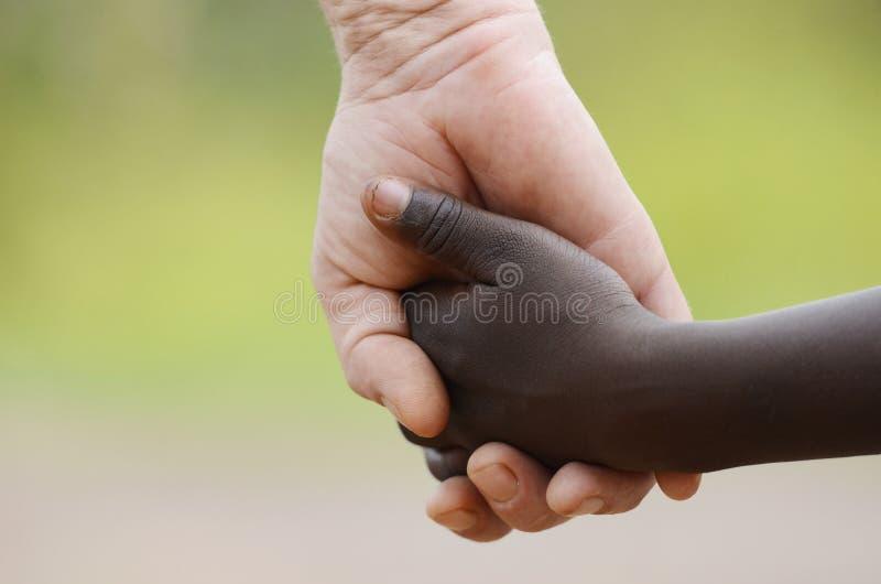 美好的和平标志-白人妇女握手的黑色孩子 库存图片