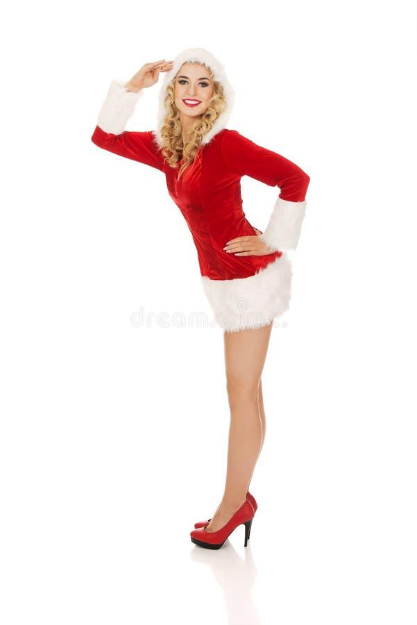 年轻美好的圣诞老人妇女致敬 免版税库存照片