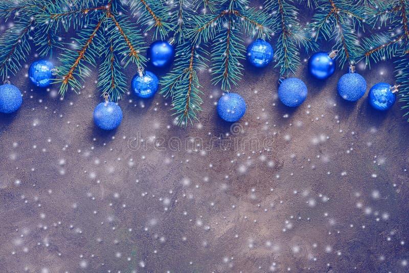 美好的圣诞节构成、用蓝色球装饰的云杉的在黑暗的织地不很细背景的分支和雪,边界 ?? 免版税库存图片