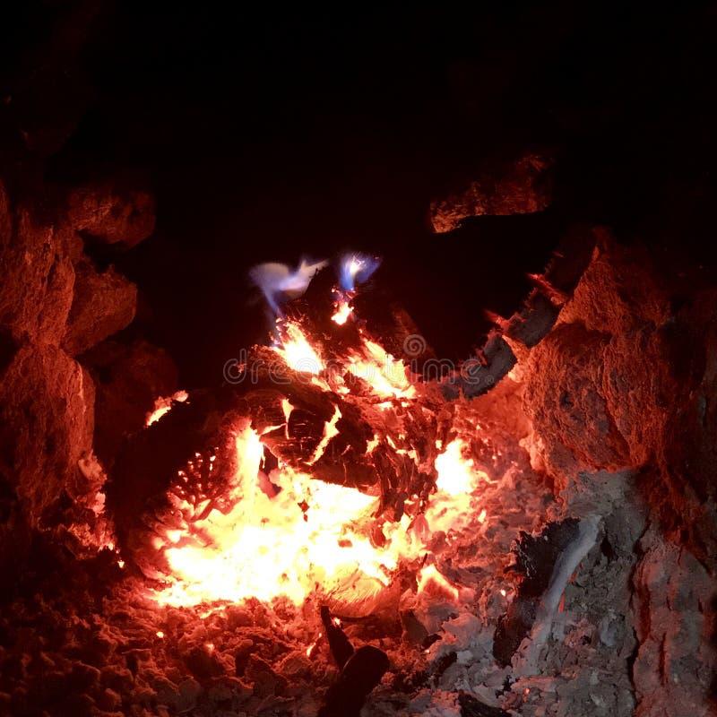 美好的在明亮的黄色火的火焰褐色木深黑色煤炭在金属火盆里面 免版税库存图片
