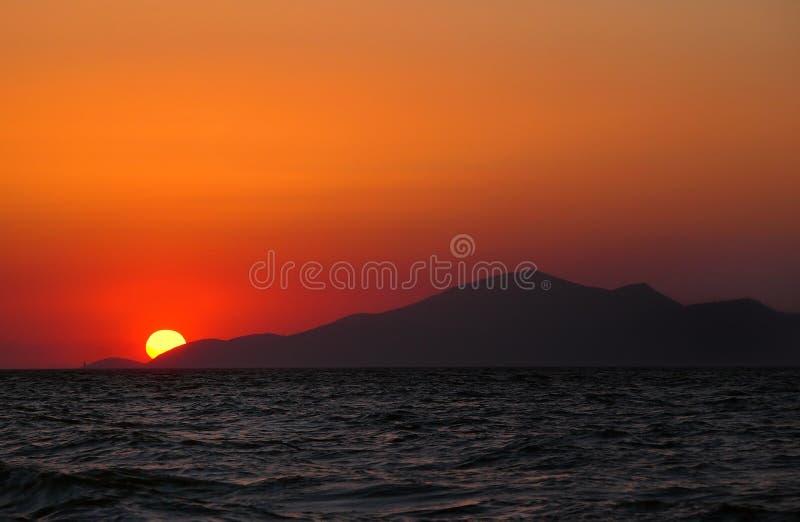 美好的地中海日落在kos海岛与橙色晚上天空和光的在黑暗的风平浪静反射了 免版税图库摄影