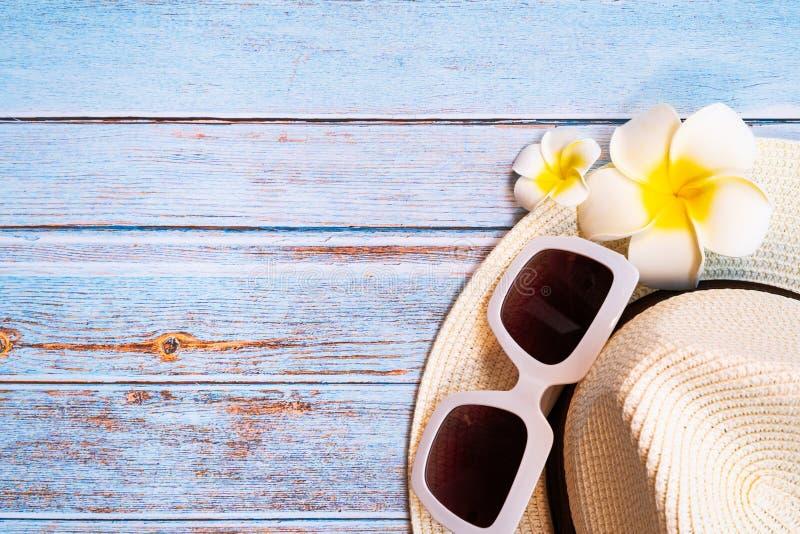 美好的夏天休假、海滩辅助部件、太阳镜、帽子和花在木背景 免版税库存照片