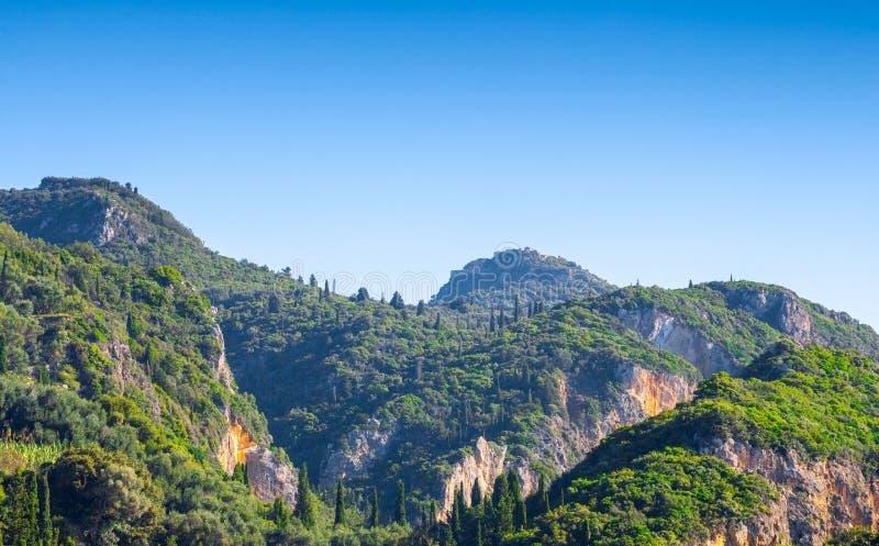 美好的夏天全景风景 赛普里斯小山和绿色山坡 某处在科孚岛 希腊 钓鱼地中海净海运金枪鱼的偏差 库存图片