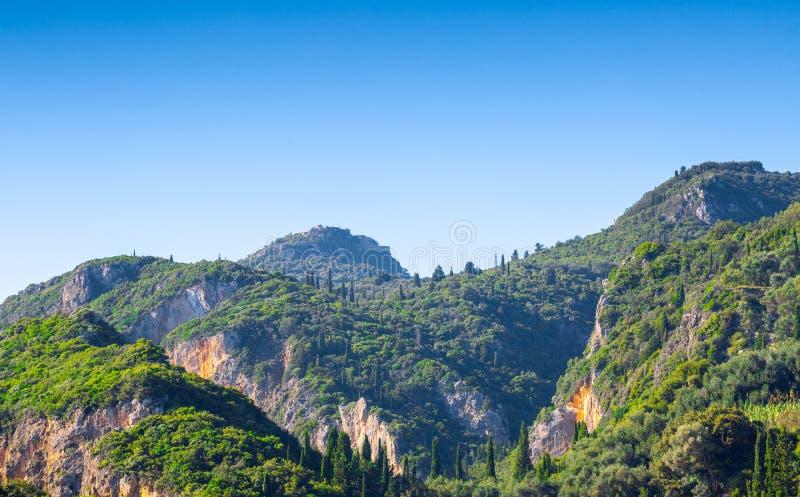 美好的夏天全景风景 赛普里斯小山和绿色山坡 某处在科孚岛 希腊 钓鱼地中海净海运金枪鱼的偏差 库存照片