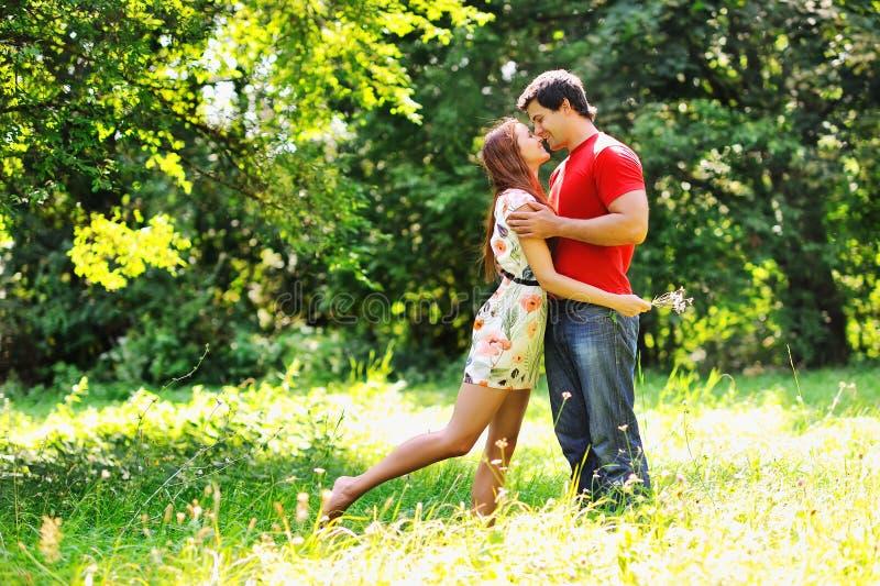 年轻美好的夫妇。笑和亲吻。夏天绿色公园 图库摄影