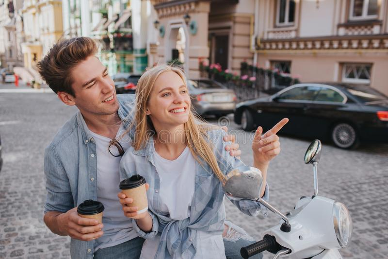 美好的夫妇一起坐看彼此的摩托车anf 他们在手上拿着咖啡 库存照片
