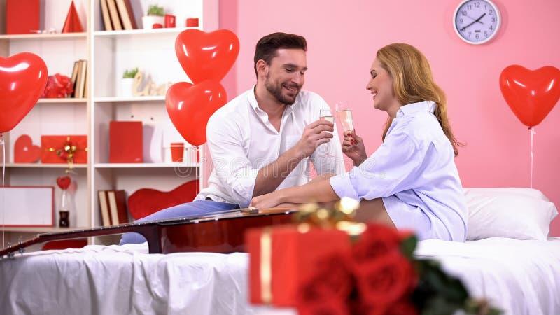 美好的夫妇使叮当响的香槟玻璃,一起庆祝情人节 免版税库存照片