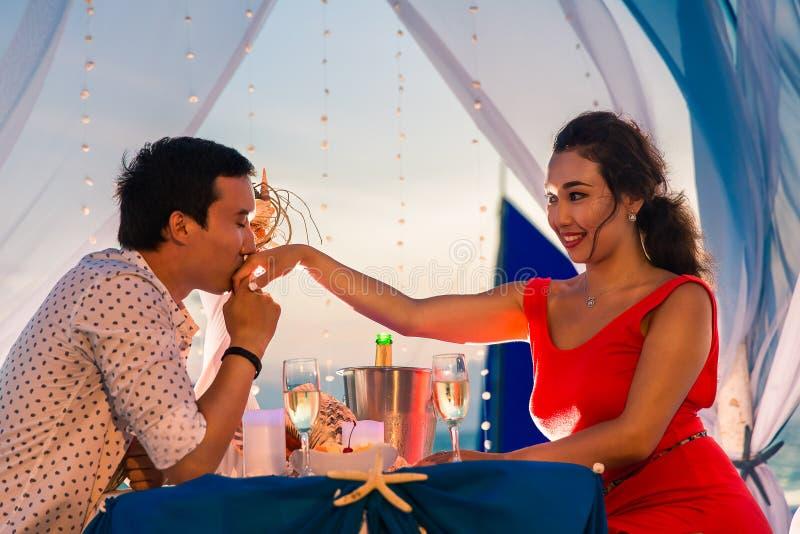 年轻美好的夫妇吃浪漫晚餐在日落 免版税图库摄影