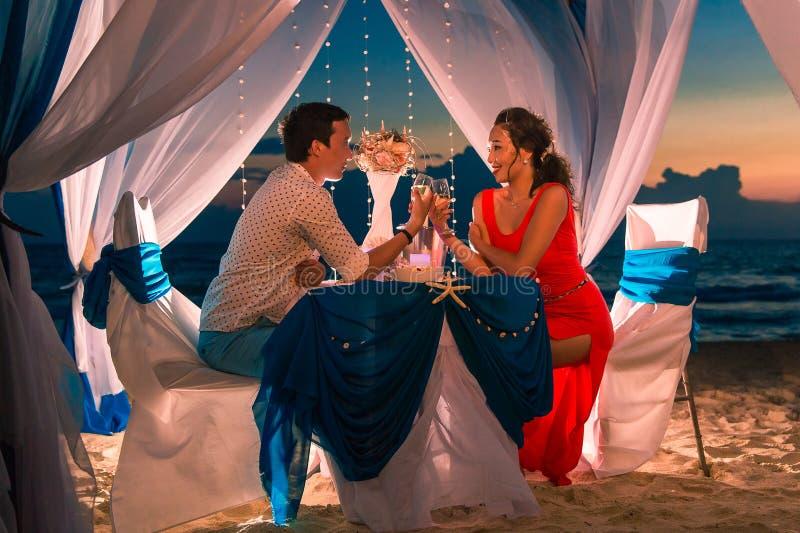 年轻美好的夫妇吃浪漫晚餐在日落 库存图片