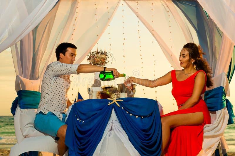 年轻美好的夫妇吃浪漫晚餐在tro的日落 免版税库存图片