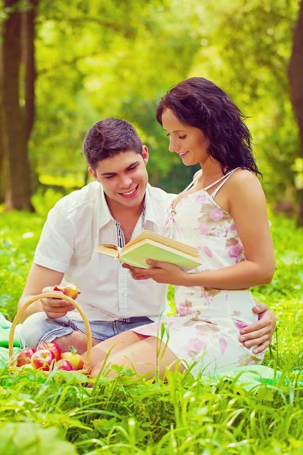 年轻美好的夫妇坐微笑的草在公园和 免版税库存图片