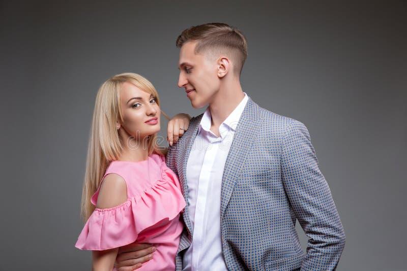美好的夫妇看彼此并且微笑着,当走下去站立灰色背景时 免版税图库摄影
