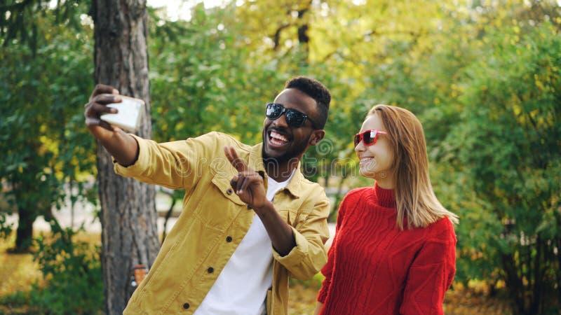 美好的夫妇非裔美国人的男人和白种人妇女在举行智能手机和摆在的公园采取selfie 库存图片