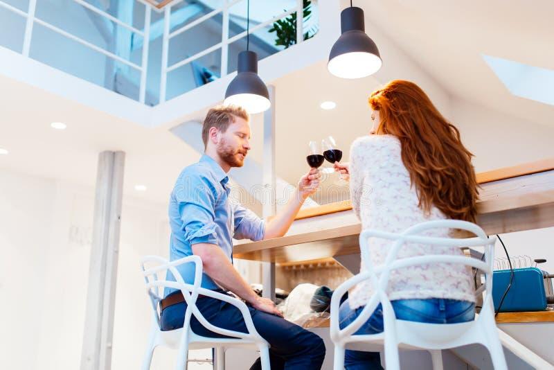 美好的夫妇饮用的酒在客厅 图库摄影
