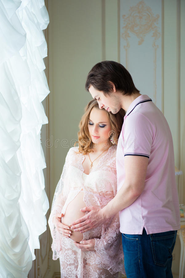 美好的夫妇,一个怀孕的少妇和一个人,拥抱充满爱,在家内部 库存照片