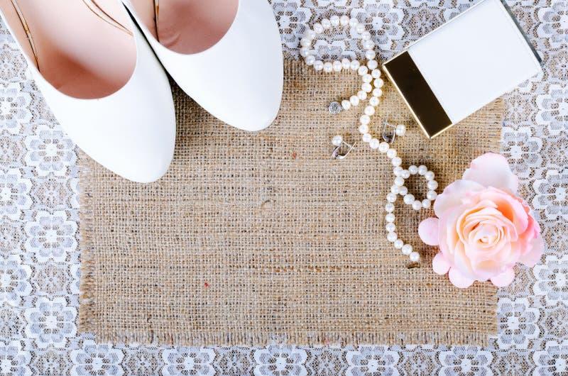 美好的套婚礼辅助部件、白色鞋子、香水、珍珠项链和耳环 库存照片