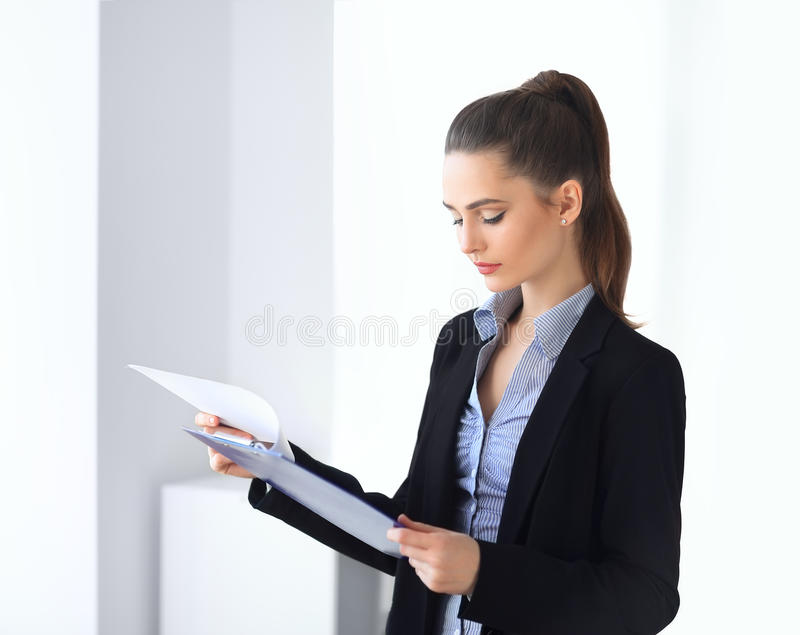 美好的女商人读书文件画象在的  免版税库存图片