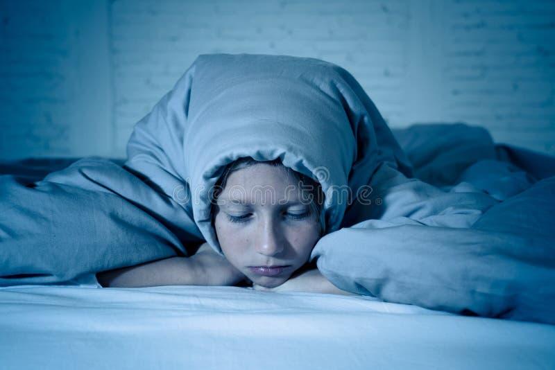 美好的女孩感觉哀伤和疲乏能睡觉在夜覆盖物头在鸭绒垫子下 库存图片