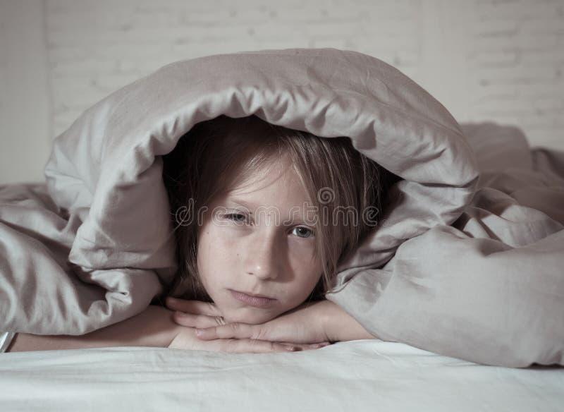 美好的女孩感觉哀伤和疲乏能睡觉在夜覆盖物头在鸭绒垫子下 免版税库存图片