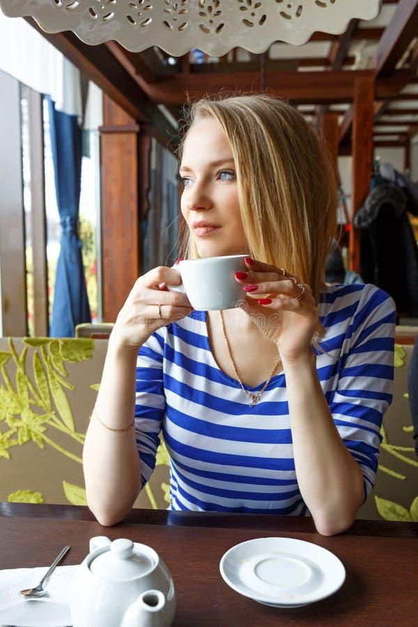 美好的女孩restingin咖啡馆和看窗口 选择聚焦 免版税库存照片