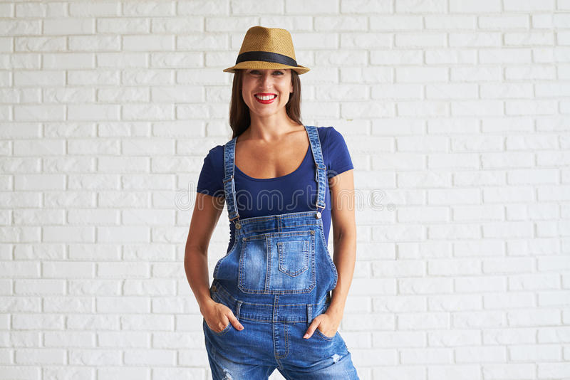 美好的女服牛仔布总体和举行她的在pocke的手 免版税库存图片