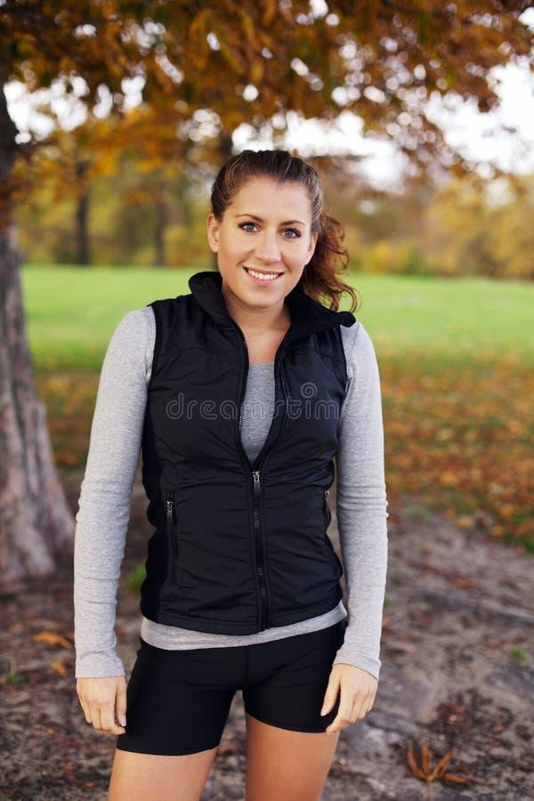 美好的妇女健身式样身分在公园 库存图片