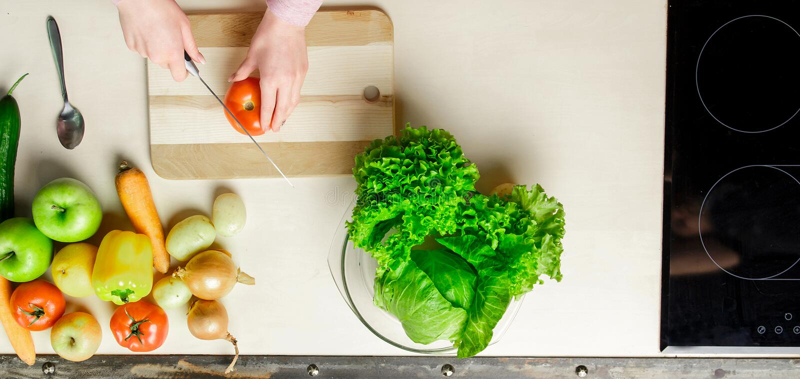 美好的妇女切片画象,切蕃茄在厨房,烹调,准备菜沙拉 免版税图库摄影