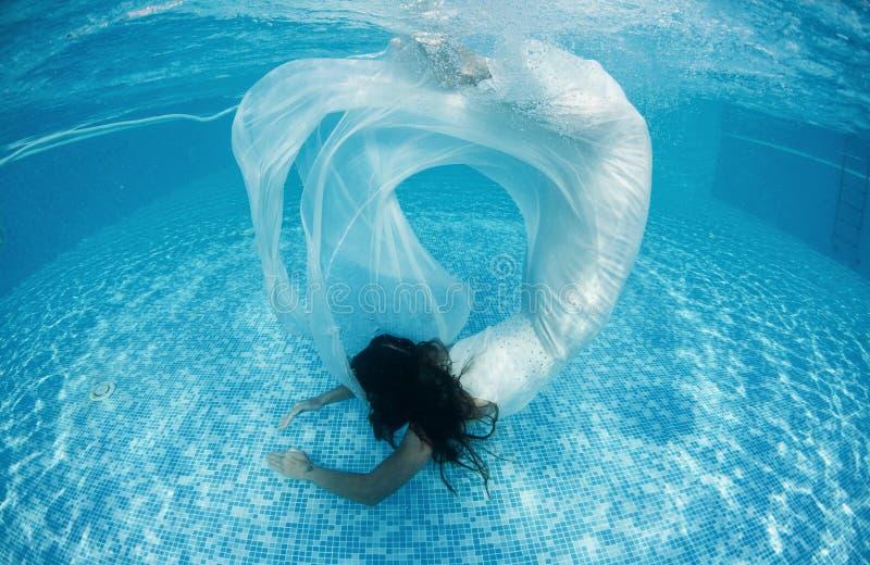 美好的妇女女孩白色礼服水下的潜水游泳蓝色晴天水池 免版税库存照片