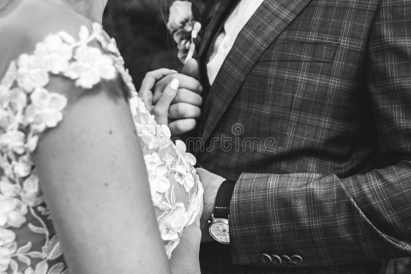 美好的婚姻的夫妇在森林有薄纱面纱和开放低后庄重装束的新娘接触蝶形领结的新郎 免版税库存图片
