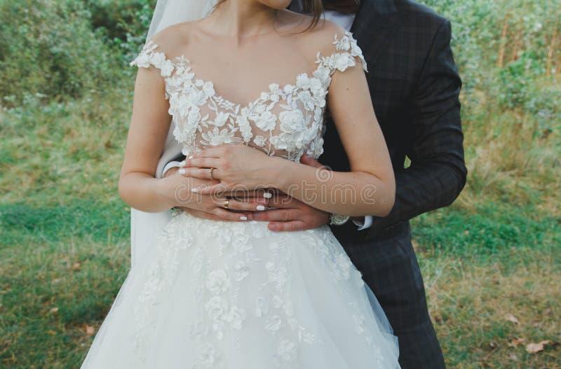 美好的婚姻的夫妇在森林薄纱面纱和庄重装束的新娘与花拥抱蝶形领结的新郎 免版税库存照片