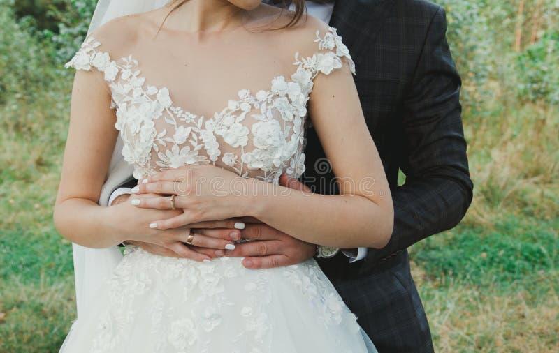 美好的婚姻的夫妇在森林薄纱面纱和庄重装束的新娘与花拥抱蝶形领结的新郎 免版税图库摄影